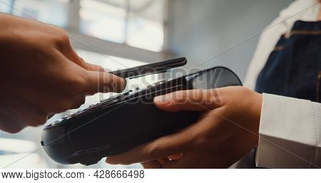 Young Asia Female Self Service Use Mobile Phone Pay Contactless With Credit Card Reader Machine At C