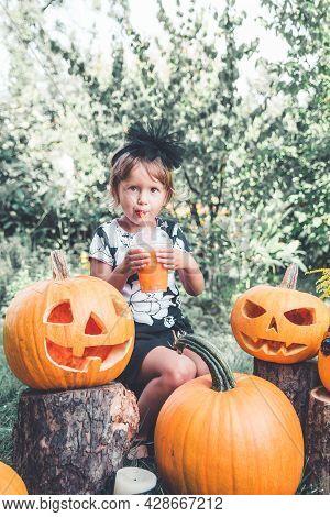 Child Dressed In Black Drinking Pumpkin Cocktail, Trick Or Treat.