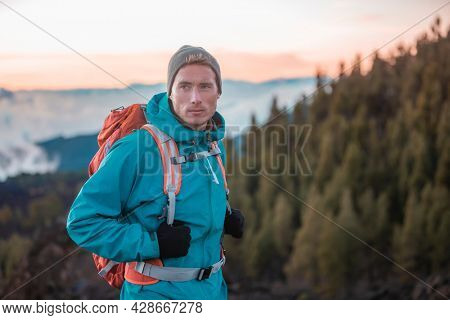 Man hiker hiking in mountain forest wearing cold weather accessories, wind jacket and backpack for camping outdoor. Guy portrait lifestyle.