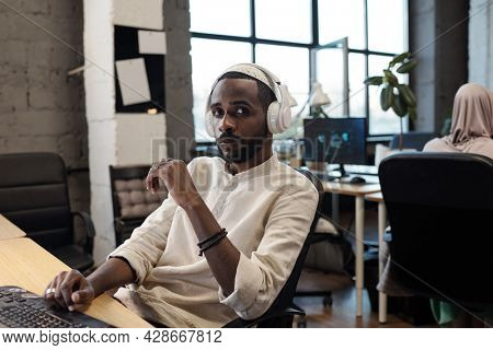 Serious young African businessman looking at camera against co-worker in office