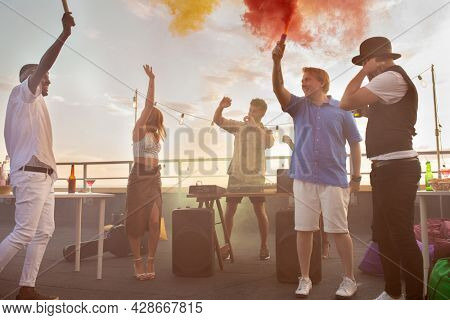 Group of cheerful multiracial people with smoke firecrackers dancing ecstatically