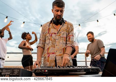 Young deejay with headphones around neck standing by soundboard in front of dancing friends