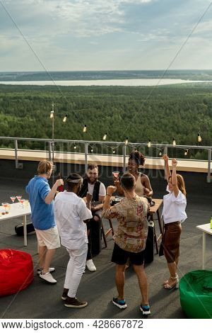 Group of ecstatic friends dancing on the roof patio while enjoying party