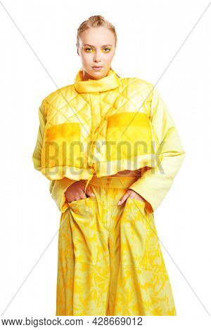 Beauty and fashion concept. Portrait of a beautiful blonde girl model with colored yellow arrows on her eyes and in bright yellow clothes on a white background. Make-up and cosmetics.