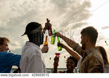 Group of happy friends clinking by bottles of beer against cloudy sky