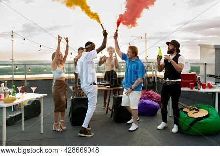 Young ecstatic friends using firecrackers with red and yellow smoke while dancing