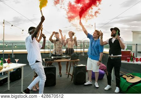 Young cheerful friends with firecrackers dancing at rooftop party