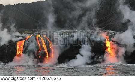 Hawaii Lava flowing into the ocean from lava volcanic eruption on Big Island Hawaii, USA. Lava stream flowing in Pacific Ocean from Kilauea volcano, USA. Seen from water.