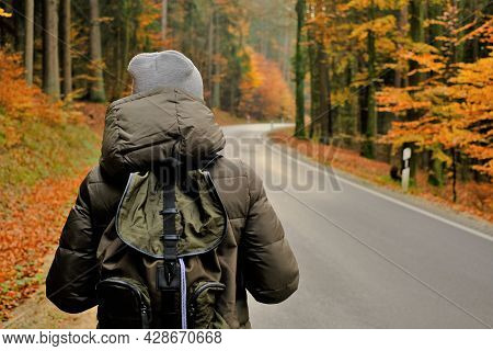 Traveler With A Backpack.hitchhiking Travel. Autumn Hikes And Travel. Girl With A Backpack Walks Alo
