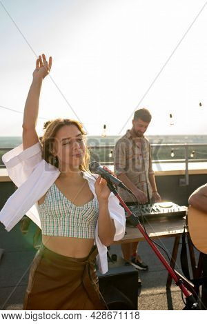 Pretty girl with raised arm singing at rooftop party against deejay by soundboard