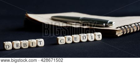 Caption Debit Credit On A Dark Surface Next To A Fountain Pen And Notepad. The Concept Of Timely Acc