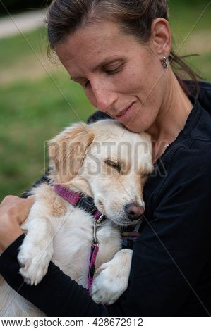Young Woman Lovingly Cuddling With Her Cute Small Dog Outside.