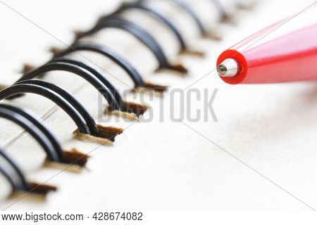 The Tip Of A Red Ballpoint Pen Rests On An Open Spring-bound Notebook. The Concept Of Learning At Sc