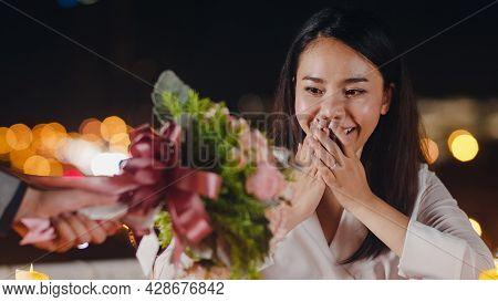 Young Asian Couple Surprise Moment With Rose Bouquet At Romantic Dinner In Rooftop Restaurant At Cit