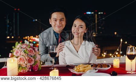 Young Asian Couple Take Photo For Memory Of Happiness Moment At Romantic Dinner In Rooftop Restauran
