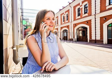 Smiling Woman Talking On Mobile Phone Outdoors.