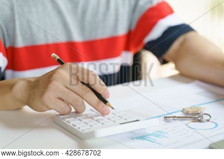 Man Presses A Calculator And Key On The Table With Report Paper To Calculate The Value During Rental