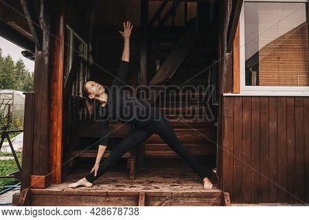 Woman Doing Yoga In Veranda. Rainy Day.