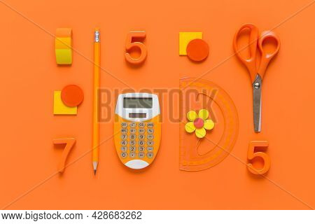 School Supplies On Orange Background, Top View. Back To School Concept.