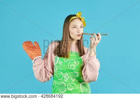 Cheerful Girl Cook In Kitchen Clothes Holds A Wooden Spoon And Cooks Dinner On A Blue Background. Yo