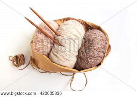 Skeins Of Yarn In Nude Colors In A Craft Bag And Knitting Needles On A Bright Background. Craft On W