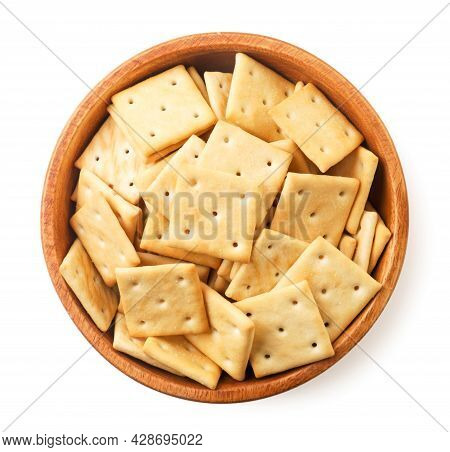 Crackers In A Wooden Plate Close-up On A White Background, Isolated. The View From Top