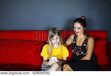 Happy Smiling Mother And Daughter Sitting On Sofa In Living Room While Using Smartphone, Cheerful Mo