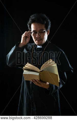 Young Asian Priest Holding Reading Holy Bible Praying On Black Background