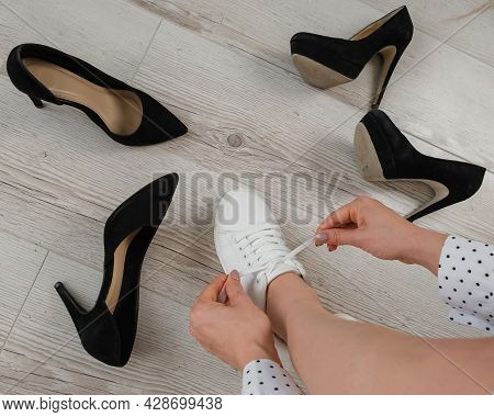 A Woman Chooses Sports Shoes Instead Of High-heeled Shoes. Sneakers Or Shoes