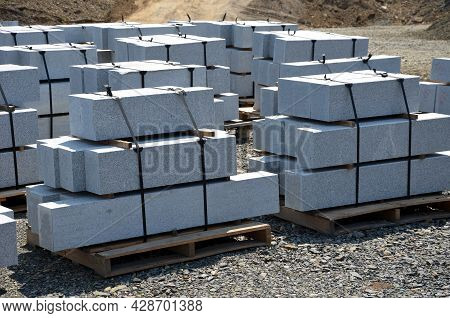Granite Curbs Of Cut Granite. Smooth Stoneware Products Stacked On A Pallet Ready For Transport To T