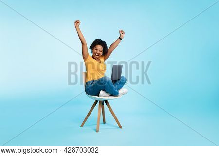 Excited Young Woman Sitting On Chair With Laptop, Raising Hands Up, Screaming, Winning Casino Bet Or