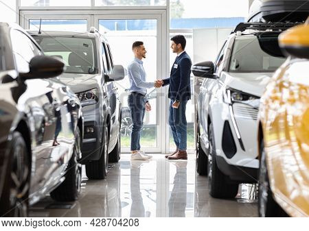 Wealthy Middle-eastern Man Shaking Sales Manager Hand In Auto Showroom