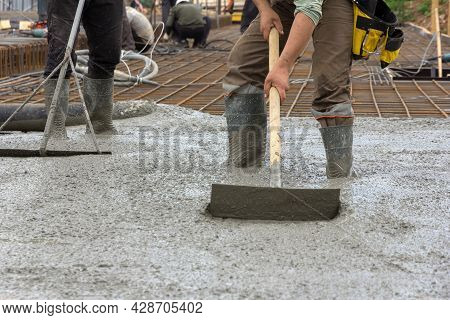 The Process Of Pouring A Monolithic Slab At A Construction Site. Construction Workers Leveling Wet C