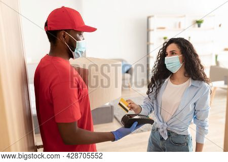 Black Deliveryman Holding Pos Terminal Lady Paying With Bankcard