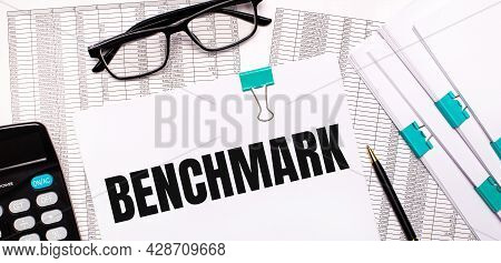 On The Desktop Are Reports, Documents, Glasses, A Calculator, A Pen And Paper With The Text Benchmar