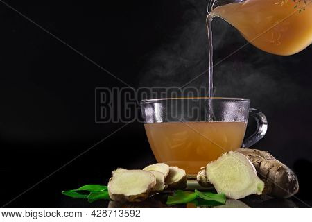 Glass Of Hot Ginger Tea With Sliced ginger Rhizomes (roots) And Leaves Placed On A Black Backgroun