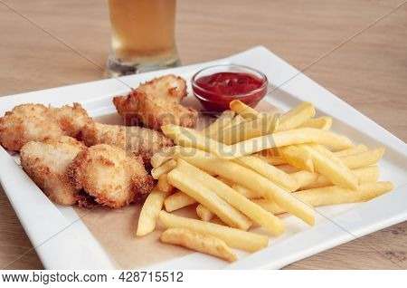 Plate Of Chicken Nuggets With French Fries. Sauce Of Ketchup