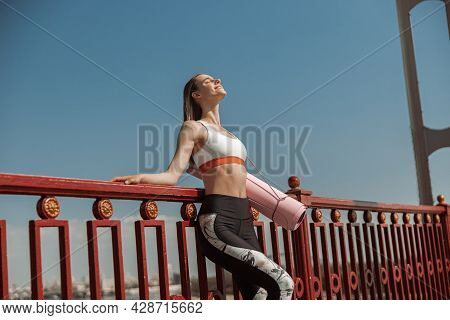 Pretty Slim Lady With Pink Mat Leans Onto Railing On Modern City Footbridge