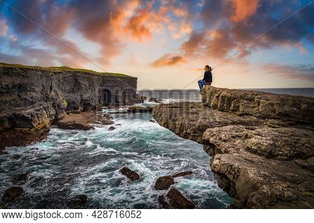 Cliffs in Kilkee at sunset, Ireland. Beautiful woman sitting on the edge of a cliff by the ocean.