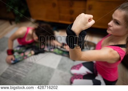 Two Girls Are Working Out, One Is Exercising Her Arm Biceps Muscles And The Other Is Doing Sit-ups.