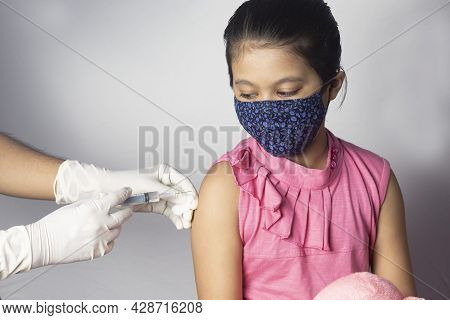 An Indian Girl Child In Nose Mask Receiving Vaccine Dose On White Background