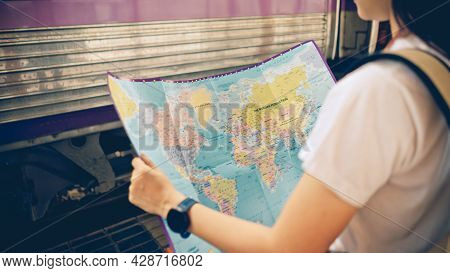 Young Female Tourist With A Backpack Searching At A Map Before Traveling By Train At The Train Stati