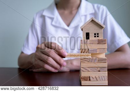 Property Insurance And Security Concept. Insurance Agent Woman's Hand Stacking Wooden Blocks On A To