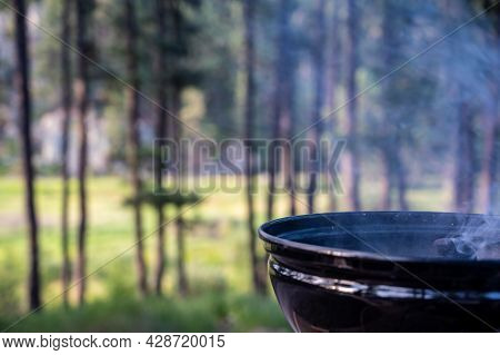 Focus On A Portable Charcoal Grill At A Campsite Overlooking A Green Forest