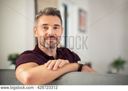 Portrait of mature man relaxing on couch at home while looking at camera. Confident mid adult man resting while sitting on sofa with copy space. Reliable businessman looking at camera.