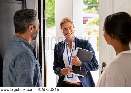 Smiling mature social counselor meeting mature couple at home. Happy multiethnic man and latin woman greeting agent at home standing near door. Successful social worker consultant on the doorstep.