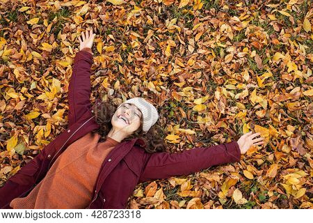 High angle view of young playful woman lying over autumn leaves with stretched arms and copy space. Happy beautiful girl lying over dry leaves and smiling with closed eyes. Autumn foliage in park.