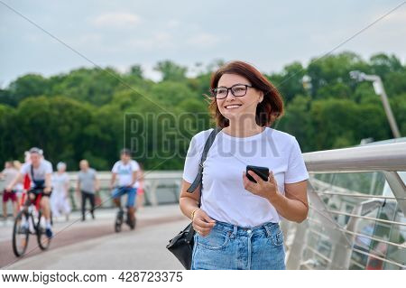 Portrait Of Middle-aged Woman Walking With Smartphone In Hand, Summer Day In City