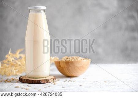 Vegan Non Dairy Alternative Milk. Oat Milk In A Mug, In A Bottle And A Bowl With Oat Flake On Grey S