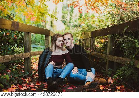 Young Caucasian Couple In Love Enjoys A Moment Of Happiness In Nature. The Young Man Hugs His Girlfr